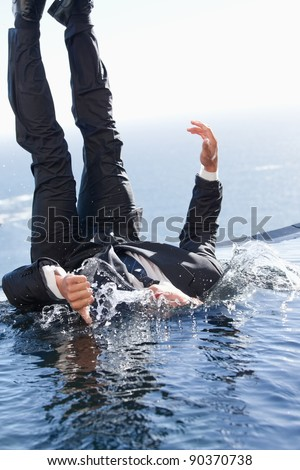 Portrait of a cheerful businessman falling into water with the thumb up - stock photo