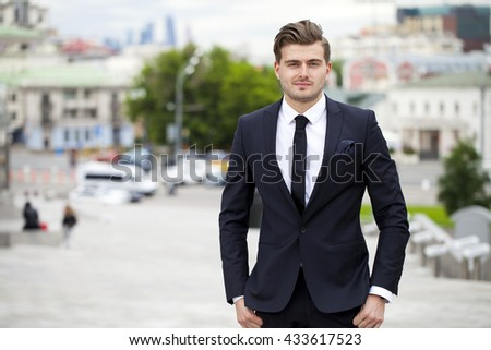 Portrait of a cheerful businessman in black suit, summer street outdoors - stock photo
