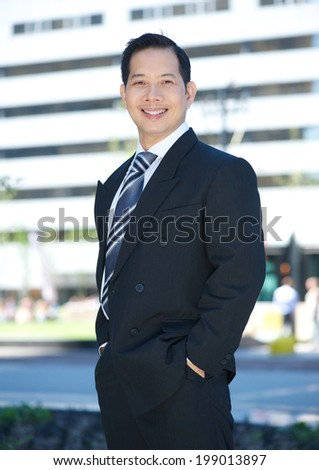 Portrait of a cheerful businessman posing outside - stock photo