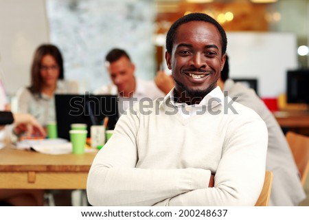 Portrait of a cheerful businessman sitting in front of colleagues - stock photo