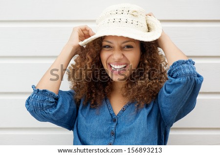 Portrait of a cheerful carefree woman laughing and wearing summer hat - stock photo