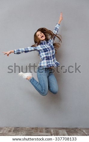 Portrait of a cheerful casual woman jumping on gray background - stock photo