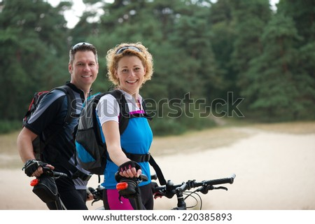 Portrait of a cheerful couple relaxing outdoors with bikes - stock photo