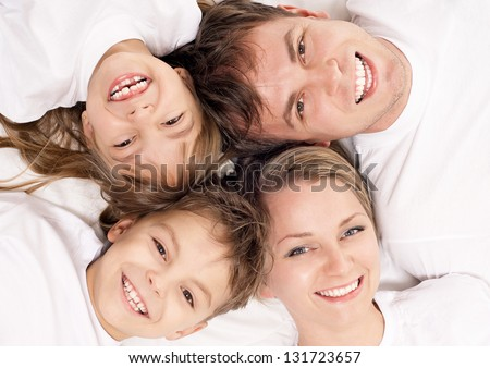 Portrait of a cheerful family having fun together lying on a bed at home - top view - stock photo