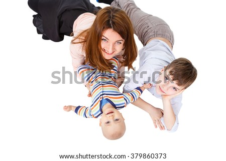 Portrait of a cheerful family mother and children having fun together lying on a floor at home - top view - stock photo