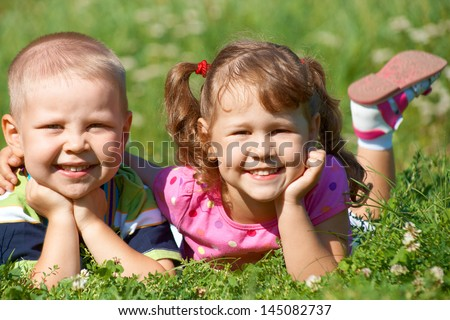 Portrait of a cheerful girl and boy lying fun in outdoor - stock photo