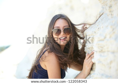 Portrait of a cheerful girl in sunglasses looking at camera on summer vacation - stock photo
