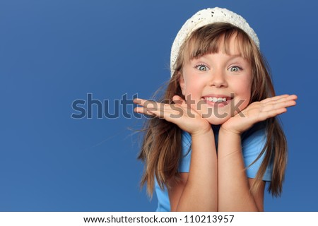 Portrait of a cheerful girl over blue sky. - stock photo