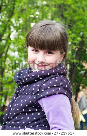 Portrait of a cheerful little baby girl in a black vest in the spring park - stock photo