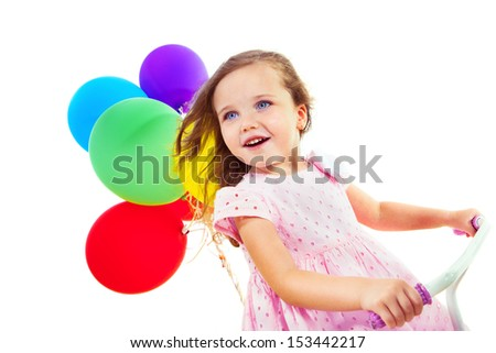 Portrait of a cheerful little girl on a bike, with colorful balloons behind - stock photo