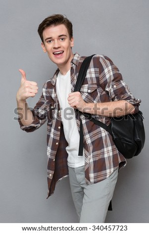 Portrait of a cheerful male student showing thumb up over gray background - stock photo