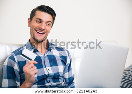 Portrait of a cheerful man holding bank card and looking at laptop - stock photo