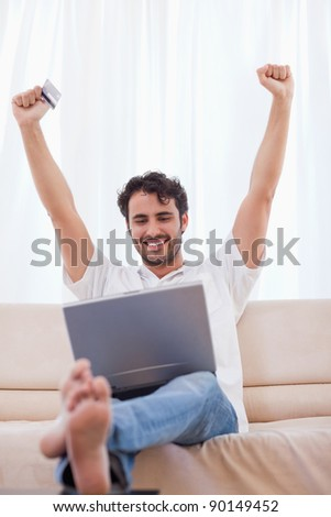 Portrait of a cheerful man shopping online in his living room - stock photo