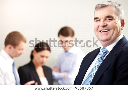 Portrait of a cheerful mature businessman smiling and looking at camera - stock photo