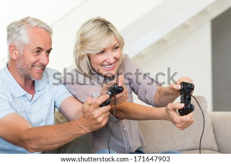 Portrait of a cheerful mature couple playing video game on sofa at home - stock photo