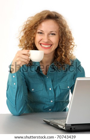 Portrait of a cheerful middle aged brunette holding coffee cup with a laptop in front - stock photo