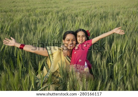 Portrait of a cheerful mother and daughter with arms out - stock photo