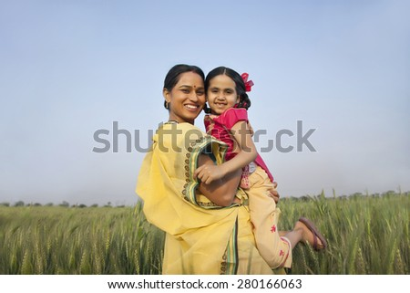Portrait of a cheerful mother carrying daughter against clear sky in a wheat field - stock photo