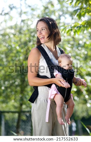 Portrait of a cheerful mother with baby in sling - stock photo