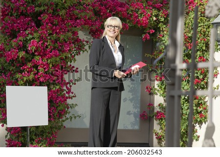 Portrait of a cheerful senior real estate agent with clipboard - stock photo