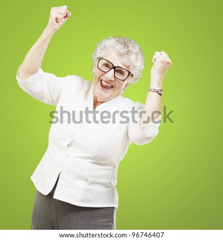 portrait of a cheerful senior woman gesturing victory over green background - stock photo