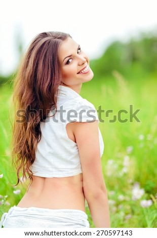 Portrait of a cheerful smiling young woman in a field - stock photo
