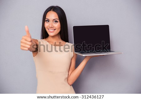 Portrait of a cheerful woman holding laptop and showing thumb up over gray background. Looking at camera - stock photo