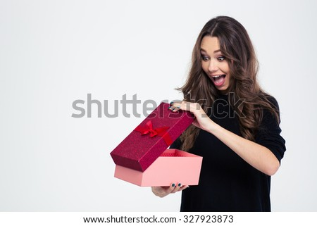 Portrait of a cheerful woman opening gift box isolated on a white background - stock photo