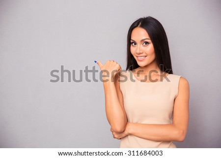 Portrait of a cheerful woman pointing finger away over gray background - stock photo