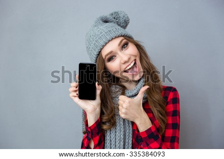 Portrait of a cheerful woman showing blank smartphone screen and thumb up over gray background - stock photo