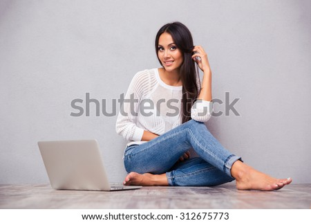 Portrait of a cheerful woman sitting on the floor with laptop on gray background - stock photo
