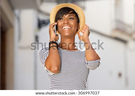 Portrait of a cheerful young black woman talking on mobile phone - stock photo