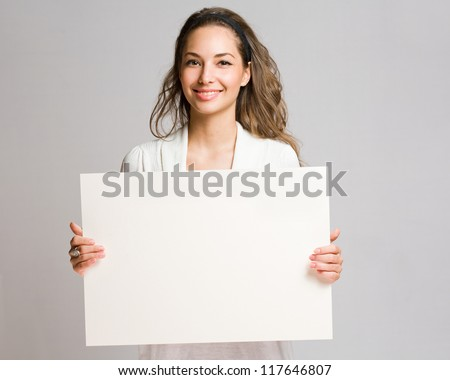 Portrait of a cheerful young brunette woman holding a white blank banner. - stock photo