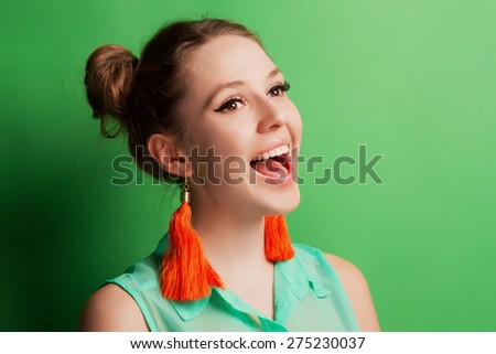 Portrait of a cheerful young girl in bright casual clothes smiling at the camera with beautiful smile.  Colorful background