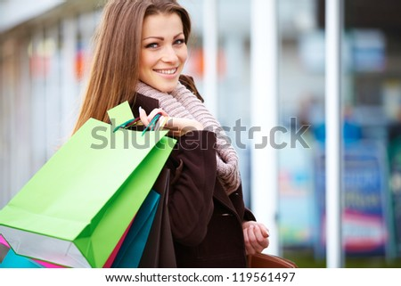 Portrait of a cheerful young lady holding shopping bags outdoor - stock photo