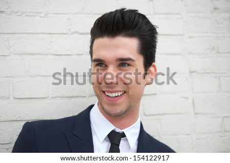 Portrait of a cheerful young man in business suit smiling outdoors - stock photo