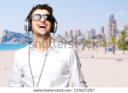 portrait of a cheerful young man listening music against a beach - stock photo