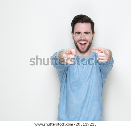 Portrait of a cheerful young man pointing fingers - stock photo