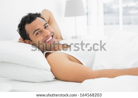 Portrait of a cheerful young man resting in bed at home - stock photo