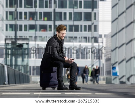 Portrait of a cheerful young man sitting on suitcase at station looking at mobile phone - stock photo