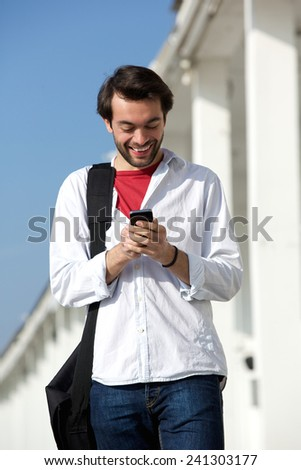 Portrait of a cheerful young man smiling and looking at mobile phone  - stock photo