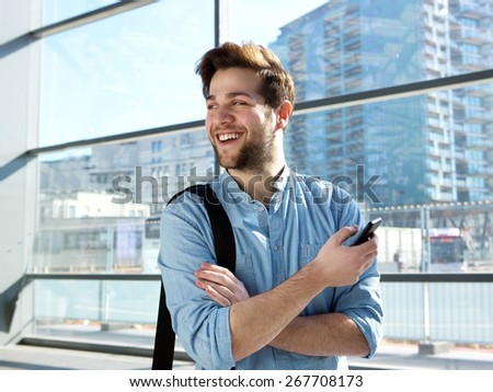 Portrait of a cheerful young man standing at station with mobile phone - stock photo