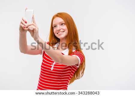 Portrait of a cheerful young pretty woman with beautiful long red hair making selfie using cellphone over white background - stock photo