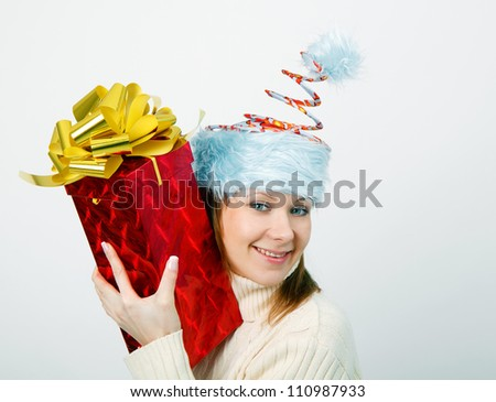 Portrait of a cheerful young woman in a funny Christmas hat with big gift in hands - stock photo