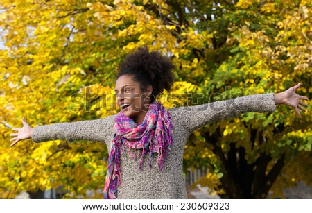 Portrait of a cheerful young woman standing outdoors with arms outstretched - stock photo