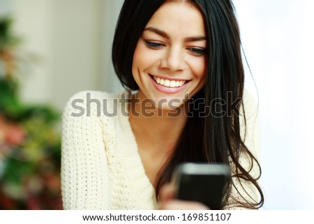 Portrait of a cheerful young woman using her smartphone - stock photo