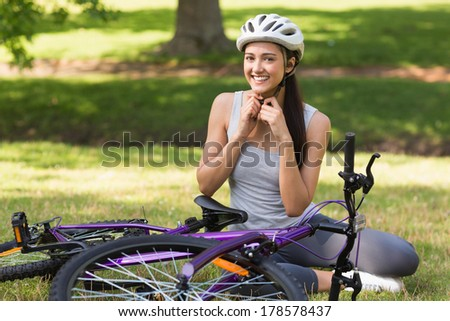Portrait of a cheerful young woman wearing helmet besides bicycle in the park - stock photo