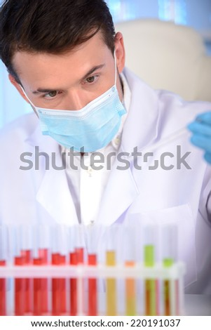 Portrait of a chemist holding a tube with liquid. Investigator checking test tubes. Man wears protective goggles - stock photo
