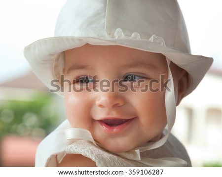 Portrait of a child a few months with white dress and hat on the day of her baptism. - stock photo