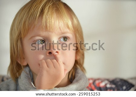 Portrait of a child aged three years old with fingers on his nose - stock photo